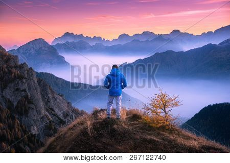 Sporty Man On The Mountain Peak Looking On Mountain Valley With Low Clouds At Colorful Sunset In Aut