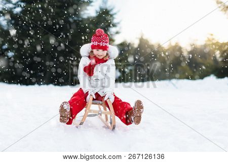 Child Sledding. Kid With Sledge. Winter Snow Fun.