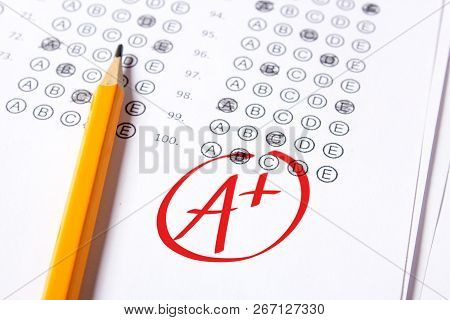 Good Grade Of A Plus Is Written With  Red Pen On The Tests