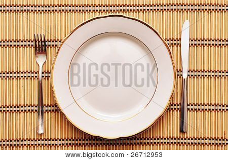 empty plate with fork knife on table
