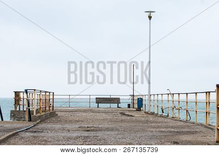 Large Stone Pier On The Beach With A Bench At The End Of The Pier.