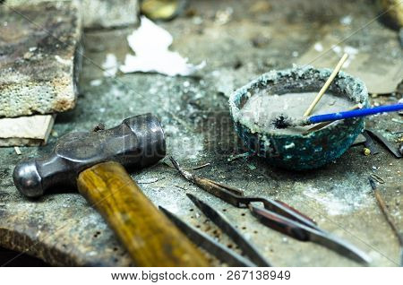 Top view of different goldsmiths tools on the jewelry workplace. Desktop for craft jewelry making with professional tools. Aerial view of tools over rustic wooden background. t-shirt