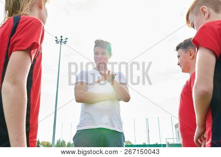 Low Angle Portrait Of Young Coach Talking To Junior Football Team Giving Instructions Before Match,