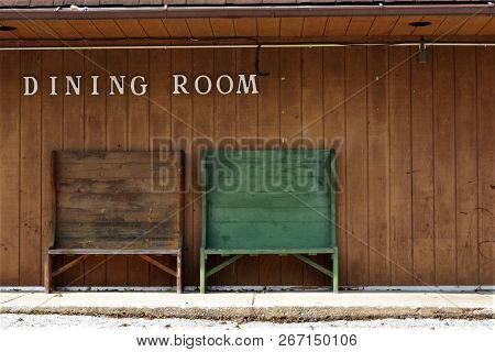 Two High Back Wooden Benches In  Front Of A Dining Room