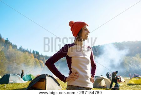 happy smiling woman in a red cap is standing in campsite in the autumn forest poster