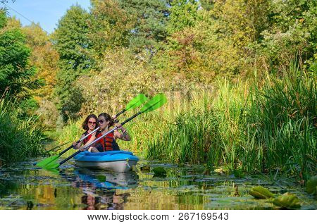 Family Kayaking, Mother And Daughter Paddling In Kayak On River Canoe Tour Having Fun, Active Autumn