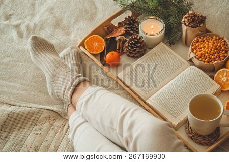 Cozy Winter Evening , Warm Woolen Socks. Woman Is Lying Feet Up On White Shaggy Blanket And Reading