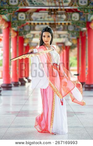 Beautiful Chinese Woman With A Traditional Suit With Blow In Her Hands, Beautiful And Belligerent Fa