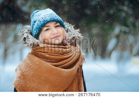 Winter Portrait Of Happy Young Woman Walking In Snowy Forest In Warm Outfit, Knitted Hat And Oversiz