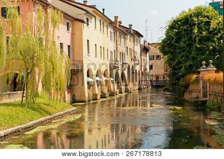 Treviso, Italy August 7, 2018: The River Flows Among The Old Buildings Of The City.