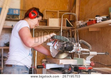Woman sawing a wood board with a circular saw. poster