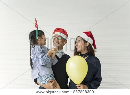 Family Asian Mother And Father With Daughter Happy Together In Livingroom At Home In Christmas Day.