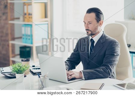 Good-looking attractive focused imposing elegant classy man in formal wear stylish style tux using pc gadget look at monitor screen sit on chair armchair at table in bright white office poster