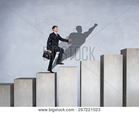 Businessman With Aspiration Seeks Forward And Up On The Career Ladder With Superhero Shadow On The W