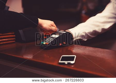Payment With Credit Card. Male Hand Puts Bankcard Into Reader