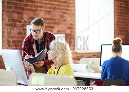 Mature employer consulting one of subordinates in front of computer monitor in office