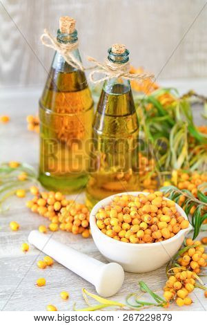 Natural, Organic Sea-buckthorn Berry In White Ceramic Mortar And Sea Buckthorn Oil In Glass Vintage