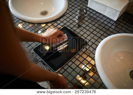 Young woman making line of cocaine before snorting it off touchpad display in bathroom