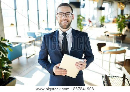 Young smiling businessman with touchpad standing in the center of modern cafe