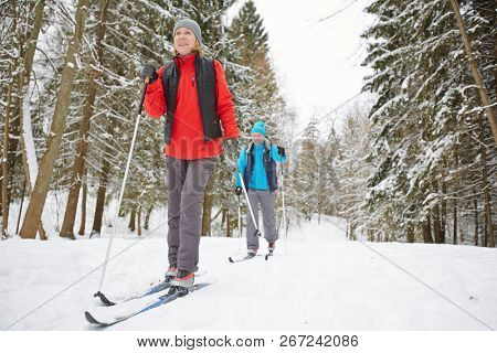 Active mature spouses in sportswear enjoying ski training on winter day in the forest