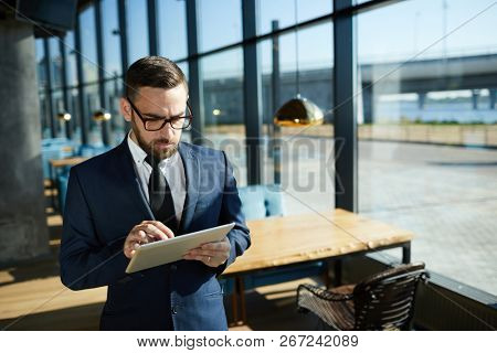 Young businessman with touchpad networking in modern cafe on summer day