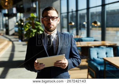 Bearded businessman in suit and eyeglasses standing in cafe while using touchpad