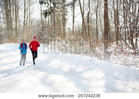 Mature couple in sportswear running down snow road in winter forest in the morning