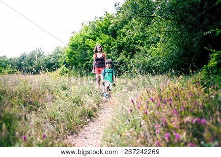 A Woman And Her Child Walk Along A Forest Trail. A Boy With A Backpack Travels With His Mother. Hike