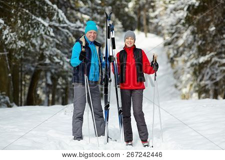 Happy senior couple in activewear looking at you while standing in winter forest among snow and trees