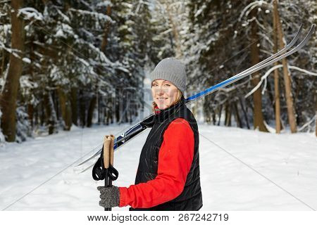 Happy mid-aged female in winter activewear carrying skiing equipment while moving to woods for training