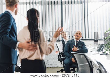 Businessman Introducing New Colleague Waving Hand And Greeting Coworkers In Office