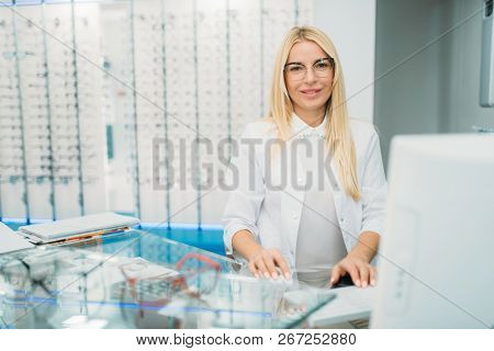 Female optician sitting at table in optics store
