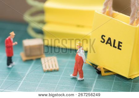 Miniature Worker Move Miniature Sale Bag Shopping Sent To Buyer. Concept Of Shopping Online Or Busin