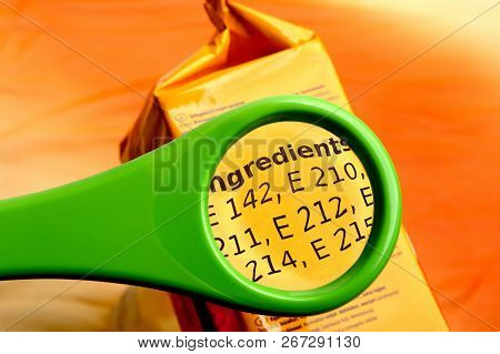 Concept Of Reading Ingredients List On Food Package With Magnifying Glass. Magnifying Glass On Food