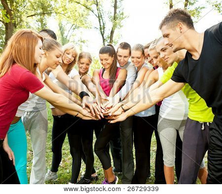 large group of young people with their hands together outdoor