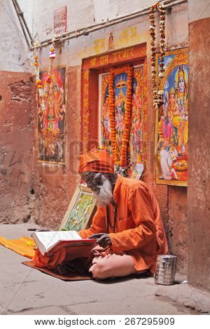 BENARES, VARANASI, UTTAR PRADESH, INDIA - FEBRUARY 13, 2013: Hindu devotee reads and reciting sacred texts
