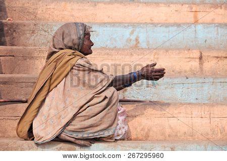BENARES, VARANASI, UTTAR PRADESH, INDIA - FEBRUARY 06, 2013: unknown poor woman begs for money from a passerby on the street in Benares during Kumbh Mela festival
