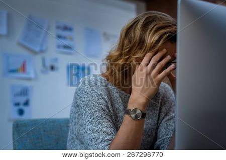 Portrait of tired business woman working at computer. Stressed casual businesswoman having headache at work. Overworked woman working late at night and holding her head in hands.