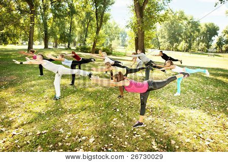 Group of young  people in park doing aerobics or warming up with gymnastics and stretching exercises