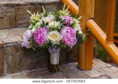 Wedding Accessories. Bride's Bouquet Of Pink Peonies And White Roses On A Stone Staircase.