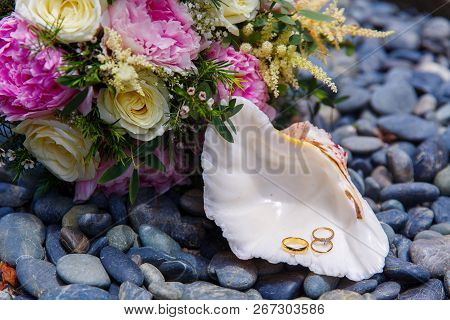 Wedding Accessories. A White Seashell With Wedding And Engagement Rings Lies On The Sea Pebbles. Wed
