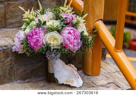 Wedding Accessories. The Bride's Bouquet Of Pink Peonies And White Roses And A Shell With Wedding Ri
