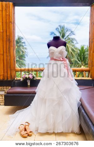Wedding Accessories. Mannequin In A Wedding Dress, Shoes And A Bouquet Of The Bride On The Window Of