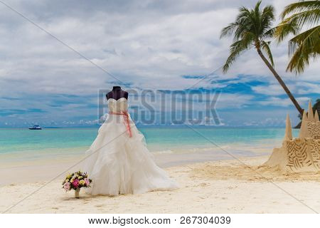 Wedding Accessories. A Mannequin In A Wedding Dress, And A Bridal Bouquet On A Tropical Beach. Sea A