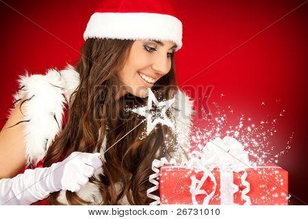 attractive santa woman with magic wand and magic Christmas present
