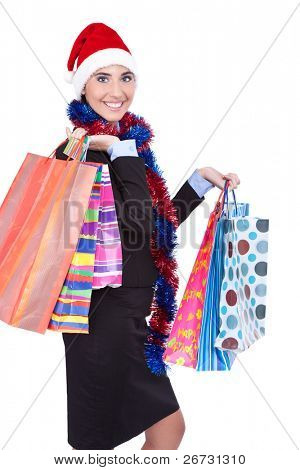 young smiling woman in Santa hat holding shopping bags, isolated over white background.
