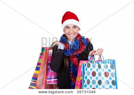 Shopping pretty young smiling woman in Santa hat holding shopping bags, isolated over white background.