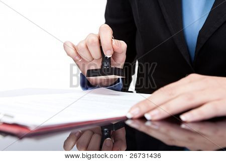 Stamping hand - Young businesswoman (or notary public) seating at the desk in office and stamping document poster