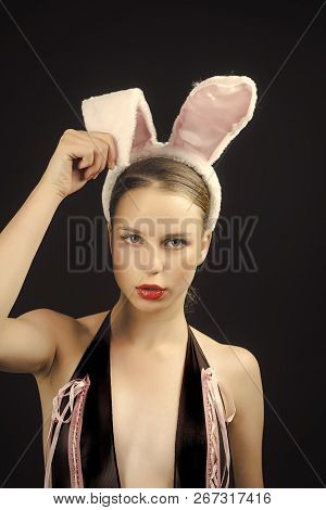 Playboy Girl Posing On Black Background. Woman With Red Lips Wearing Rabbit Ears. Sexy Bunny Model.