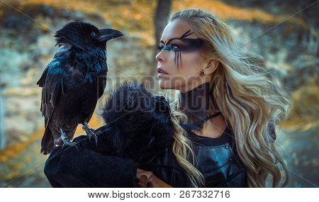 Beautiful black crow, Viking blonde woman with shield and sword, braids in her hair.